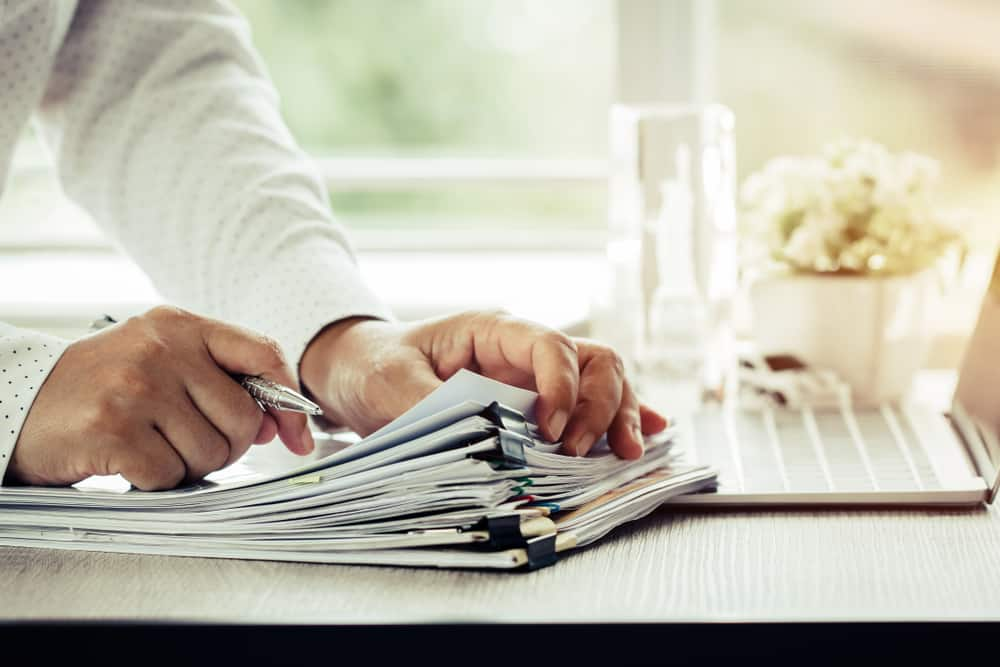 Businessman,Hands,Holding,Pen,For,Working,In,Stacks,Of,Paper